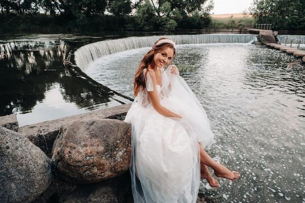Een elegante bruid in een witte jurk, handschoenen en blote voeten zit in de buurt van een waterval in het park en geniet van de natuur