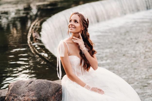 Een elegante bruid in een witte jurk, handschoenen en blote voeten zit in de buurt van een waterval in het park genieten van de natuur. een model in een trouwjurk en handschoenen in een natuurpark. wit-rusland.