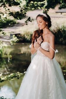 Een elegante bruid in een witte jurk, handschoenen met een boeket op een waterval in het park, genietend van de natuur. model in een trouwjurk en handschoenen in het bos. wit-rusland