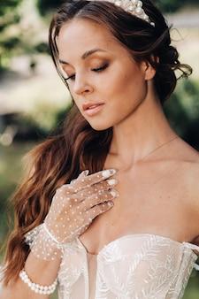 Een elegante bruid in een witte jurk, handschoenen met een boeket op een waterval in het park, genietend van de natuur.