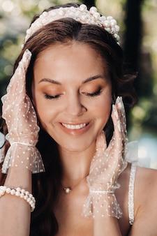 Een elegante bruid in een witte jurk, handschoenen met een boeket op een waterval in het park