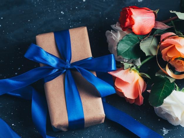 Een elegante geschenkdoos vastgebonden met een blauw lint, een fles rode wijn op een donkere tafel met een boeket rozen, een romantische avond. valentijnsdag cadeau