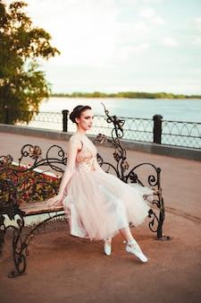 Een elegante jonge vrouw in een prinsessenjurk zit in een roze jurk op een bankje aan de rivieroever en...