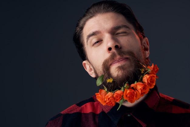 Een elegante man in een geruite overhemd bloeit op een donkere achtergrond van de baardclose-up.