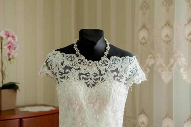 Een elegante trouwjurk op een paspop in een mooie lichte kamer