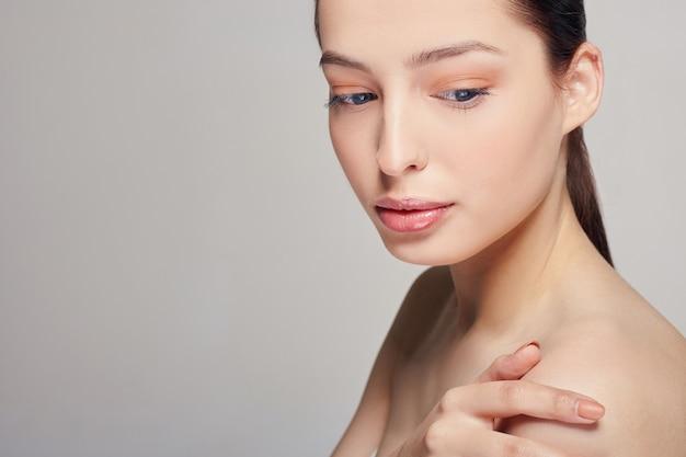Een elegante, verfijnde vrouw met volle lippen, donker haar en stralende schone delicate huid omhelsde zichzelf