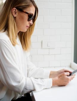 Een elegante vrouw die een smartphone, een verbindings en een communicatie concept gebruikt
