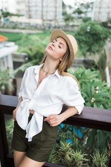 Een elegante vrouw in een zomerjurk staat op het balkon, leunend op de reling en een strohoed op haar hoofd
