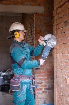 Een elektricien-bouwvakker in een beschermende helm op een werkplek werkt met een slijper.