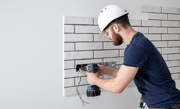 Een elektricien bouwvakker in overall met een boormachine tijdens de installatie van stopcontacten. home renovatie concept.