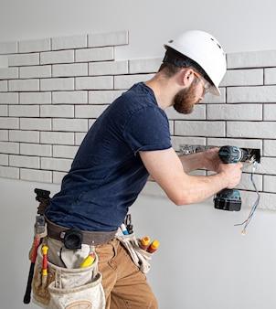 Een elektricien bouwvakker in overall met een boormachine tijdens de installatie van stopcontacten.