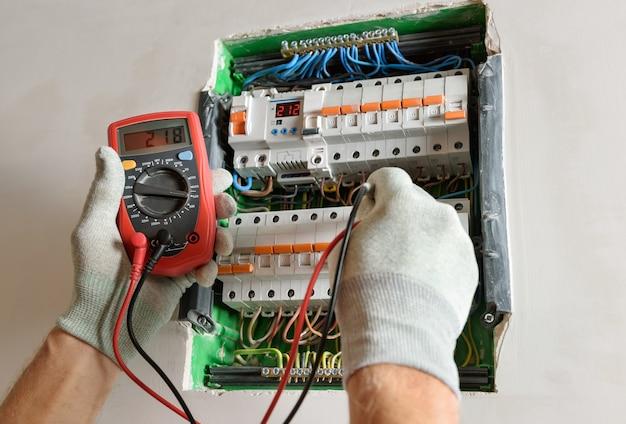 Een elektricien controleert met een multimeter de juistheid van de aansluiting van de stroomonderbreker.