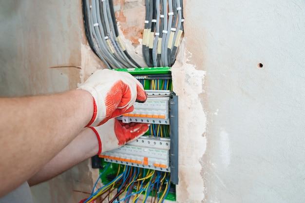 Een elektricien die de zekeringen in de schakelkast installeert.