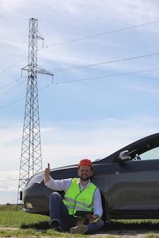 Een elektricien in de velden in de buurt van de hoogspanningslijn. de elektricien beheert het proces van het oprichten van hoogspanningslijnen. de monteur in een helm en een reflecterende vorm speciale handschoenen op het werk.