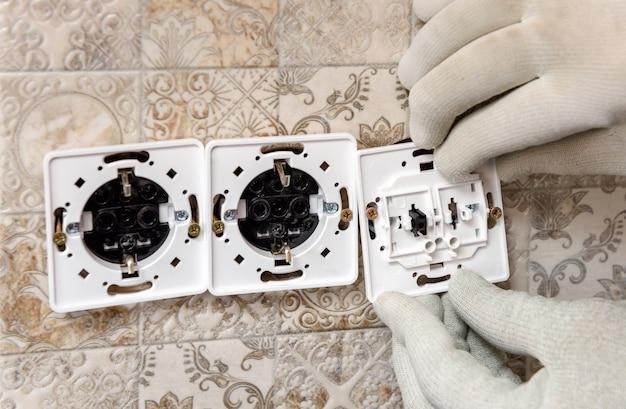 Een elektricien installeert schakelaars en stopcontacten aan de muur.