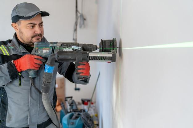 Een elektricien maakt een uitsparing in de muur voor een stopcontact dat is gemarkeerd met een laserpointer