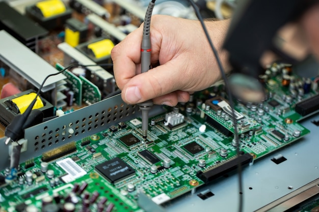 Een elektricien meet de spanning tijdens het repareren van een lsd-tv in een servicecentrum
