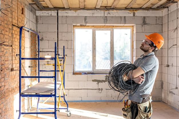 Een elektricien met een helm kijkt naar de muur terwijl hij een elektrische kabel vasthoudt.