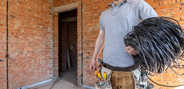 Een elektricien met een helm kijkt naar de muur terwijl hij een elektrische kabel vasthoudt