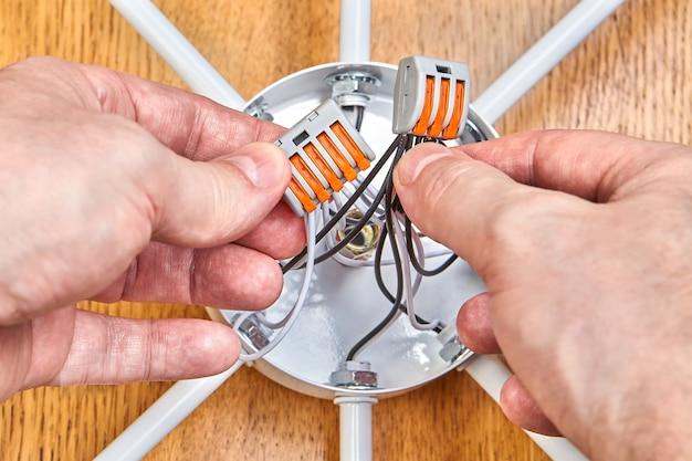 Een elektricien monteert de bedrading in de schakelkast van de plafondlamp met behulp van een aansluitblok met hendels.