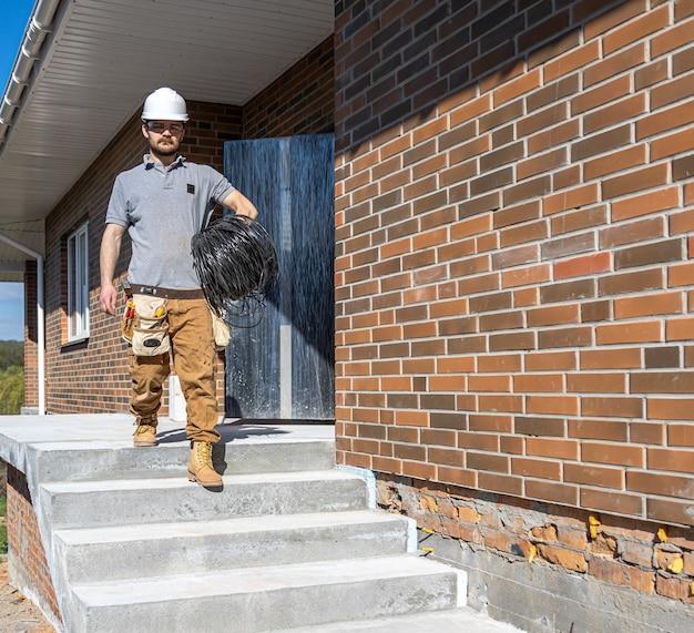 Een elektricien onderzoekt een bouwplaats terwijl hij een elektriciteitskabel in zijn hand houdt op de bouwplaats