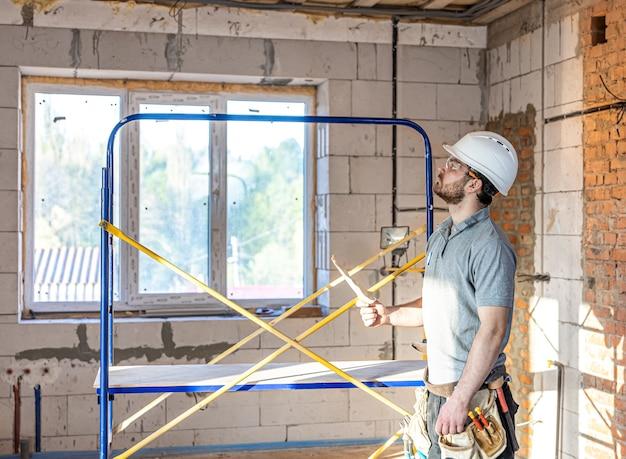Een elektricien onderzoekt een bouwtekening op een werkplek.