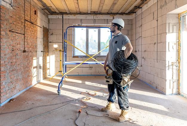 Een elektricien onderzoekt een constructietekening terwijl hij een elektrische kabel in zijn hand houdt op een werkplek.