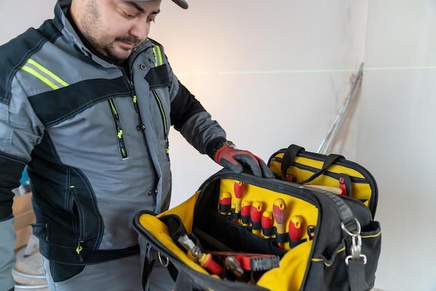 Een elektricien opende een tas een tas met een speciaal gereedschap en onderzoekt de inhoud