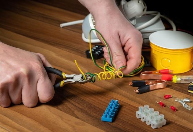 Een elektricien snijdt de draad door met een diagonale tang. werkomgeving op de werkplaatstafel