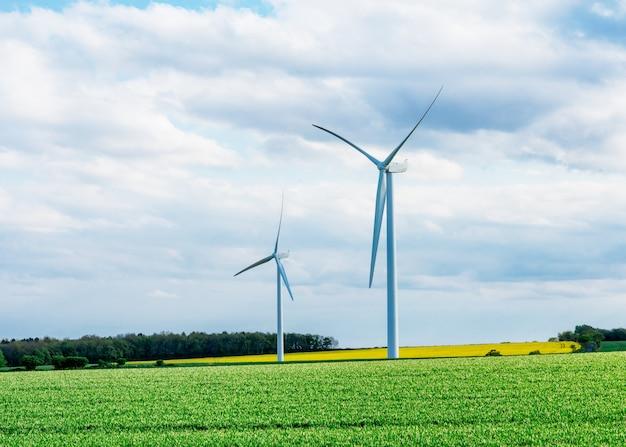 Een elektriciteit die windmolens op het gele en groene gebied produceert tegen bewolkte blauwe hemel in engeland