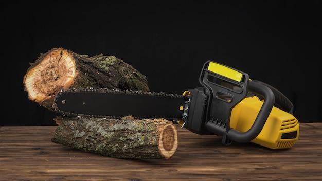 Een elektrische kettingzaag en twee gezaagde boomstammen op een houten tafel. elektrisch gereedschap voor houtverwerking.