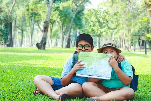 Een elementaire aziatische jongenszitting op het gazon in de tuin die een kaart houdt om de informatie te bestuderen.