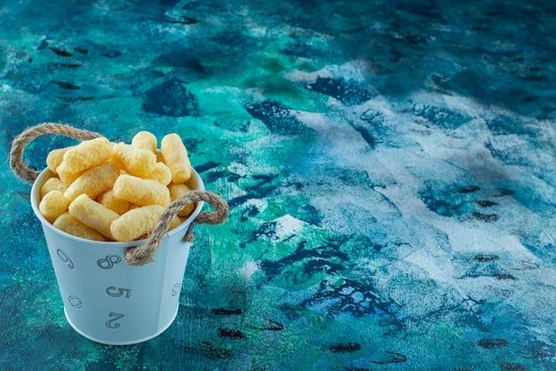 Een emmer maïsstengels, op de marmeren tafel.