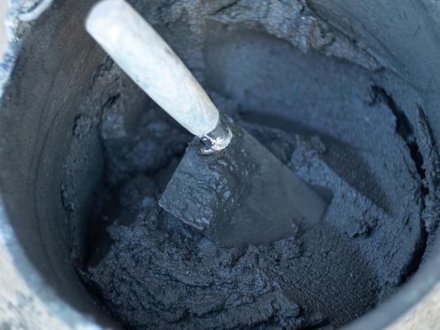 Een emmer met een metselwerkmengsel voor het leggen van stenen op een bouwplaats. cement in een emmer