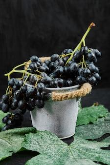 Een emmer met zwarte druiven met bladeren op een donkere ondergrond