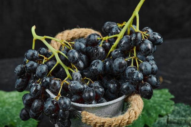 Een emmer met zwarte druiven met bladeren op zwarte ondergrond, close-up