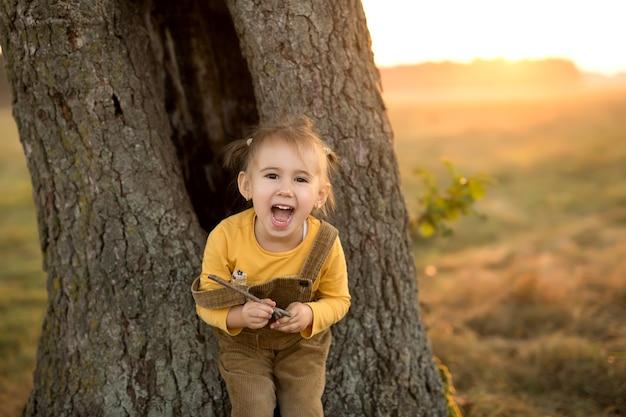Een emotioneel kind bij een grote boomstam bij zonsondergang