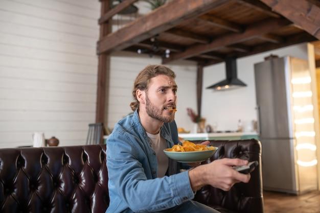 Een emotionele man die chips eet terwijl hij tv kijkt
