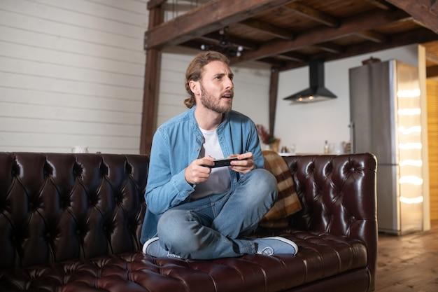 Een emotionele man die thuis een videogame speelt