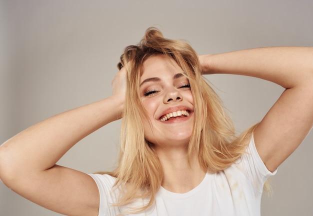 Een energieke blondine raakt het haar op haar hoofd met haar handen aan. hoge kwaliteit foto