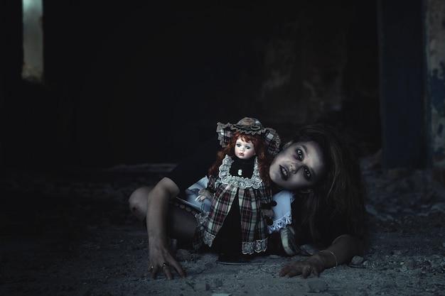 Een eng meisje met een pop op de vloer in een verlaten huis. een idee voor halloween