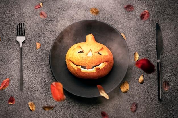 Een enge oranje pompoen op tafel, een zwarte vork met een lepel, een bord en een achtergrond. halloween-feestuitnodiging voor een restaurant of voor een feest in een bar.