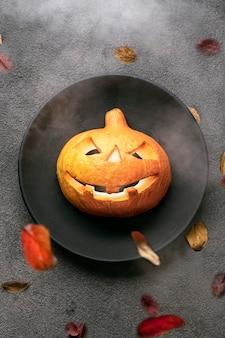 Een enge oranje pompoen op tafel, gloeiende ogen, een zwarte plaat en een achtergrond. halloween-feestuitnodiging voor een restaurant of voor een feest in een barkaart.