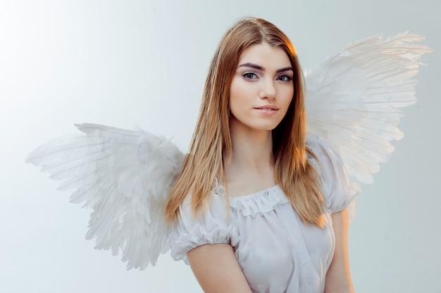 Een engel uit de hemel. jong, prachtig blond meisje in de afbeelding van een engel met witte vleugels.