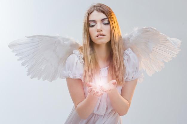 Een engel uit de hemel met licht op de handpalmen. jong, prachtig blond meisje in de afbeelding van een engel met witte vleugels.