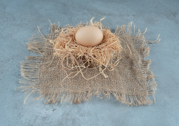 Een enkel ei op een kleine stapel stro op marmeren achtergrond. hoge kwaliteit foto