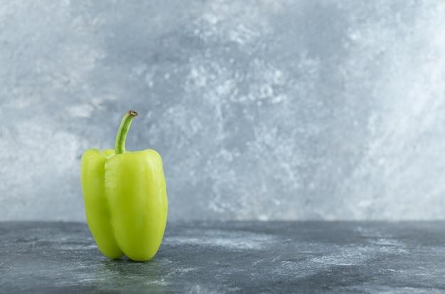 Een enkele groene verse peper op een grijze achtergrond.