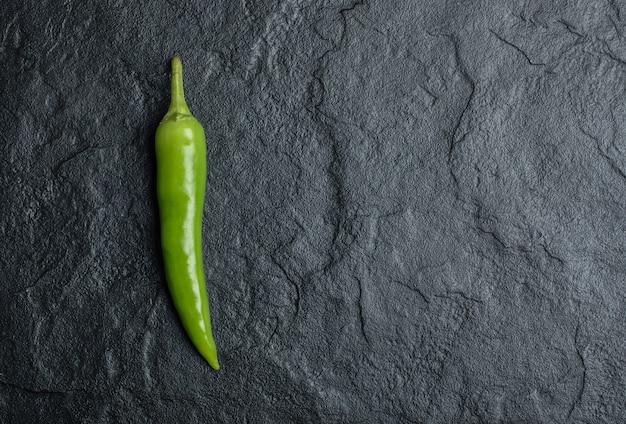 Een enkele hete chili pepers op zwarte achtergrond.