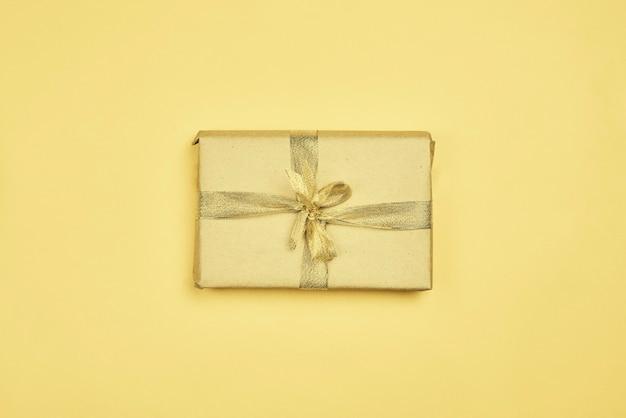 Een enkele kerstcadeau doos op gele achtergrond. kerstcadeau verpakt op ambachtelijk papier en vastgebonden met gouden lint