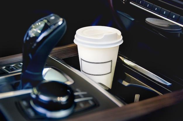 Een enkele papieren koffiekop in de bekerhouder van de auto.